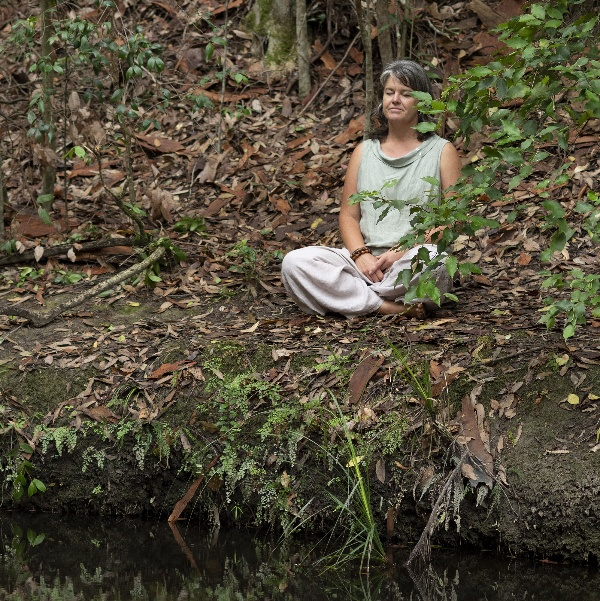 A women sitting in a forest. Button for Tricia D Walker free audio nature meditatioins. meditating.